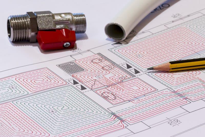 La scrivania con i montaggi idraulici, il casco ed il pavimento radiante progettano immagine stock libera da diritti