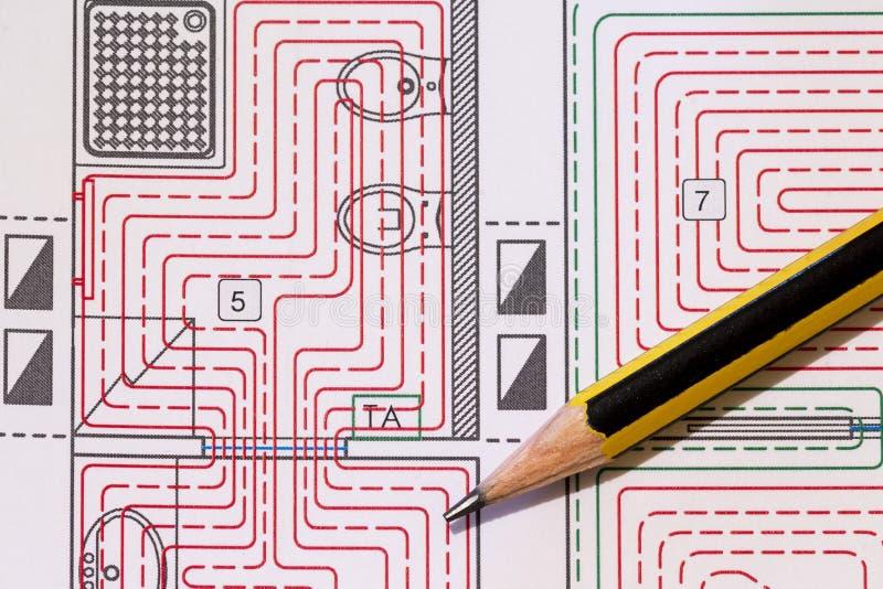 La scrivania con i montaggi idraulici, il casco ed il pavimento radiante progettano fotografia stock