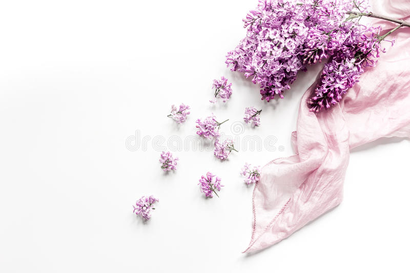La scrivania della donna con il fiore del lillà e della sciarpa progetta il modello bianco di vista superiore del fondo fotografie stock