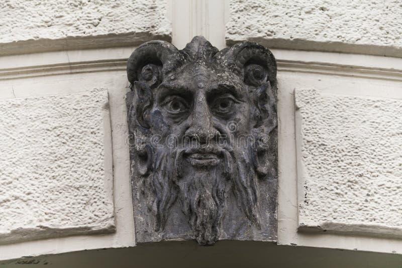 La sculpture de Lucifer font face avec des klaxons Fond de la façade de mascarone de démon d'architecture du bâtiment mauvais d'é photos libres de droits