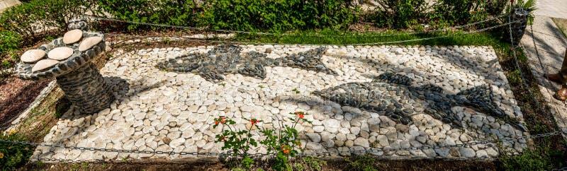 La sculpture en pierre, deux pêchent et cinq miches de pain, église du bâti des béatitudes, Israël photographie stock libre de droits