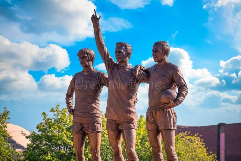 La scultura bronzea unita della trinità al vecchio stadio di Trafford a Manchester, Regno Unito immagini stock