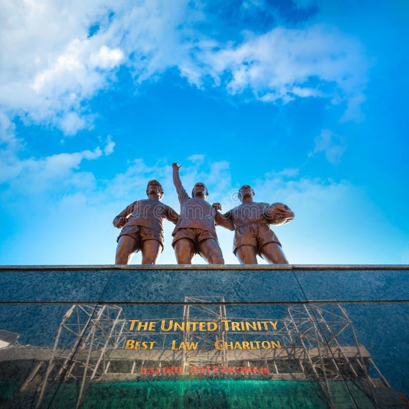 La scultura bronzea unita della trinità al vecchio stadio di Trafford a Manchester, Regno Unito fotografie stock libere da diritti