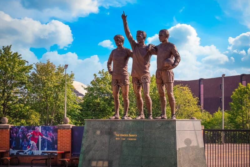 La scultura bronzea unita della trinità al vecchio stadio di Trafford a Manchester, Regno Unito fotografia stock libera da diritti