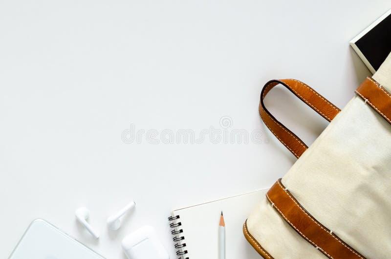 La scuola porta la borsa con il libro dello studente, il taccuino, la matita e lo smartphone moderno con le cuffie senza fili per fotografie stock