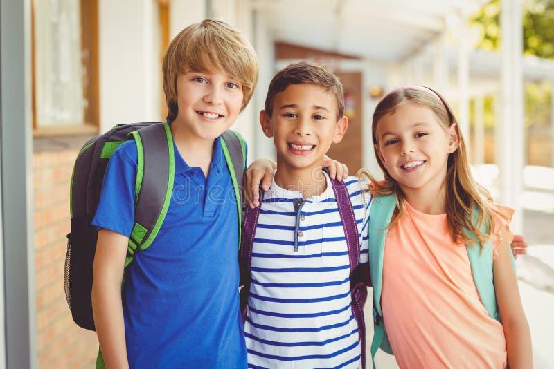 La scuola sorridente scherza la condizione in corridoio della scuola con il braccio intorno immagini stock