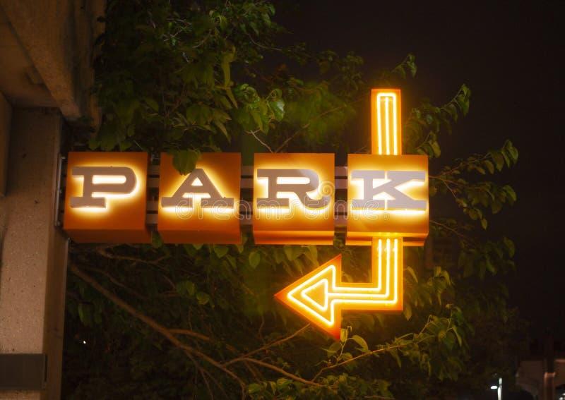 La señal de neón azul y anaranjada dice el parque aquí fotos de archivo libres de regalías