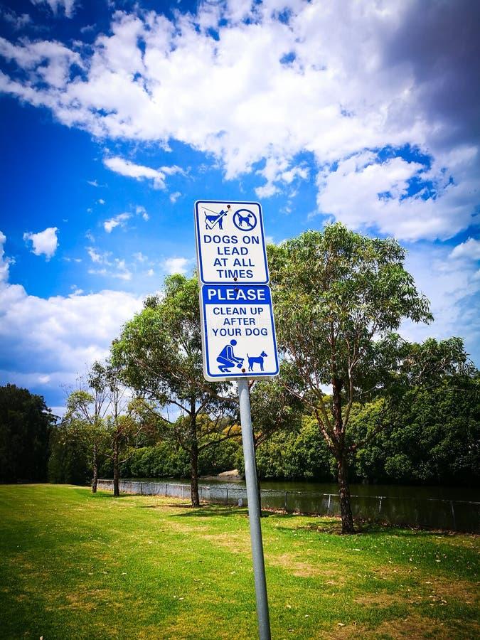 La señal de peligro para los perros en la ventaja limpia siempre y por favor después de su perro fotografía de archivo