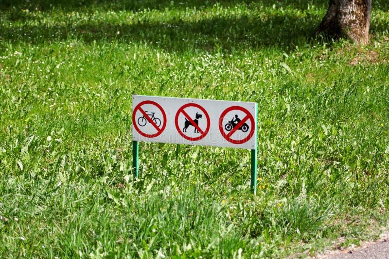 La señal de tráfico/las muestras o el símbolo de ningunos perros caseros basura, bici y motocicletas no se permite en hierba en p foto de archivo libre de regalías