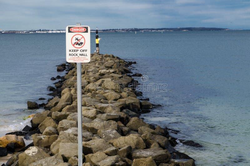 La señal de tráfico para la actividad de alto riesgo, evita la pared costera rocosa del océano foto de archivo