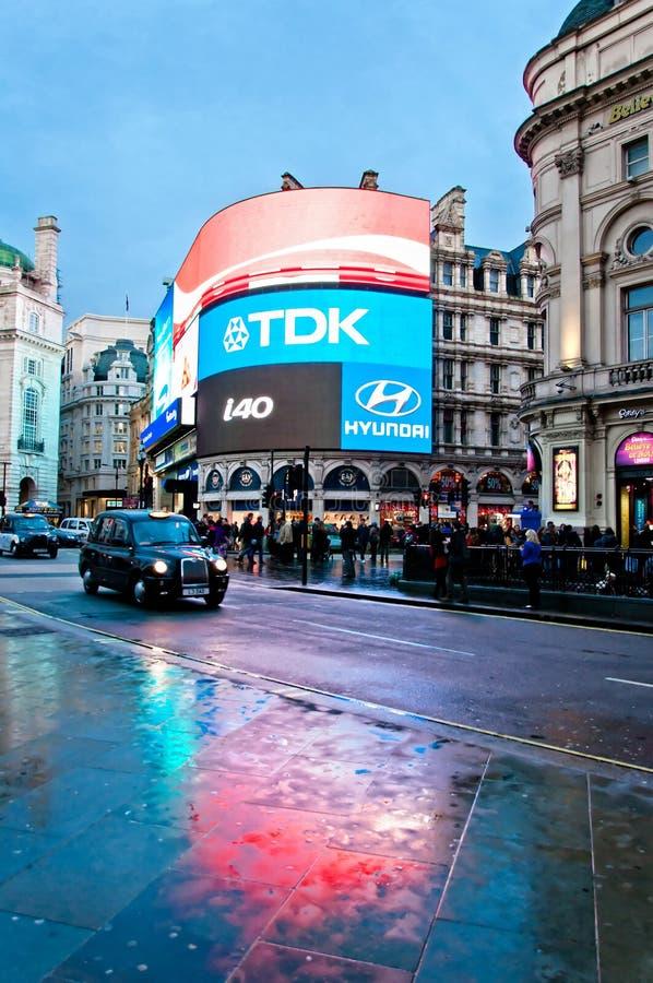 La señalización de neón del circo de Piccadilly reflejó en la calle con taxy imagen de archivo