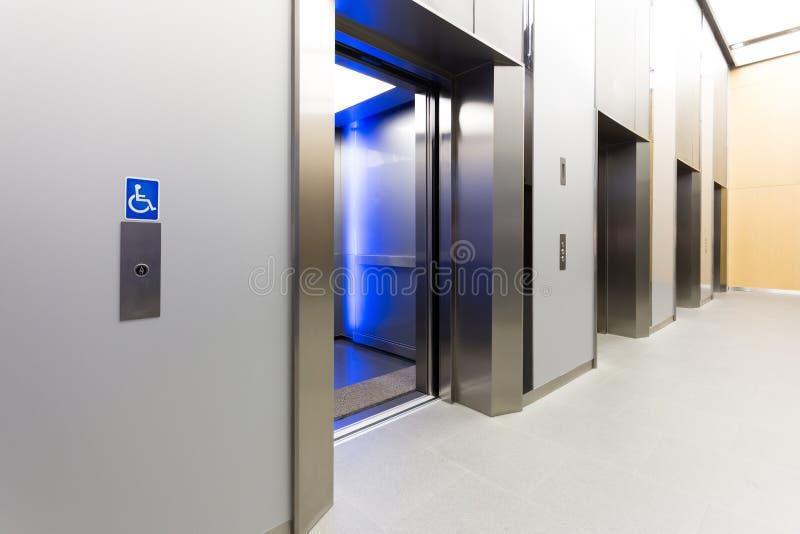 la señalización discapacitada, elevador de acero moderno abrió cabinas en un busin foto de archivo