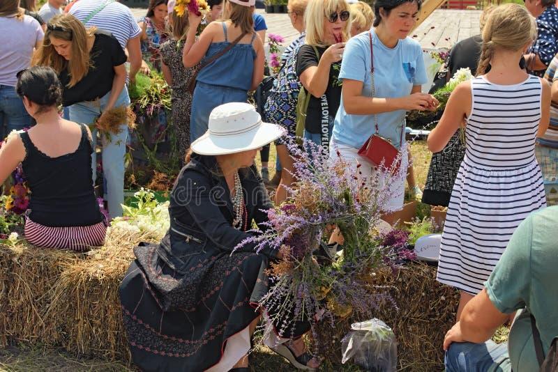 La señora acaba de acabar de hacer su guirnalda La gente está tejiendo las guirnaldas de las flores salvajes Concepto del verano imagen de archivo