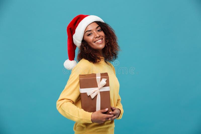 La señora africana joven feliz se vistió en el suéter caliente que sostenía el regalo imagen de archivo