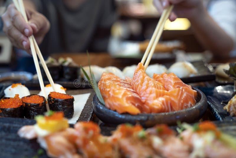 La señora asiática come un sashimi y un sushi de color salmón de los pescados en restaurante japonés imagenes de archivo