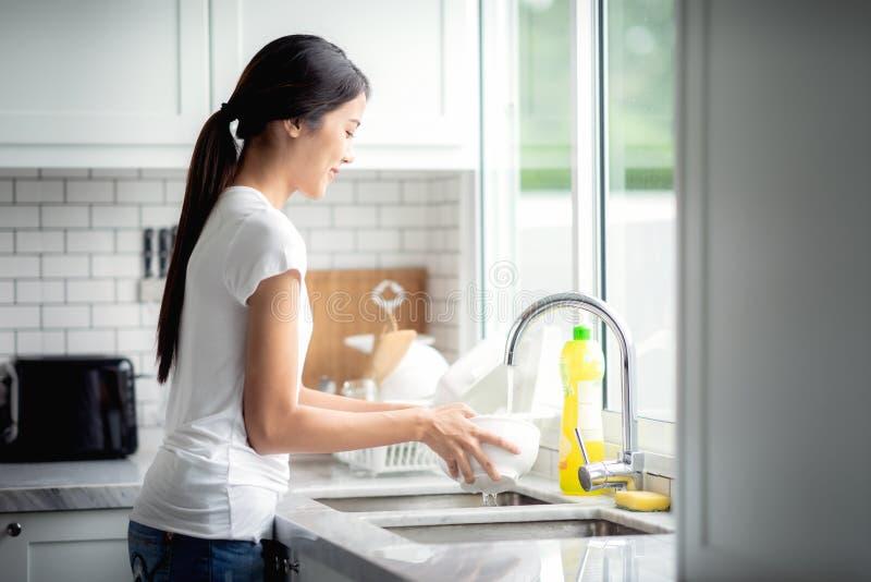 La señora asiática lava un plato imagen de archivo