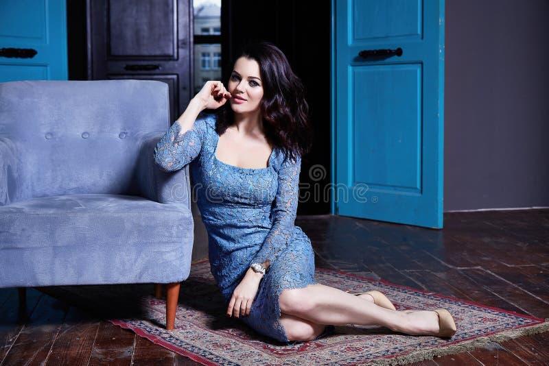 La señora atractiva hermosa se sienta en el piso en el color azul f de la sala de estar fotos de archivo libres de regalías