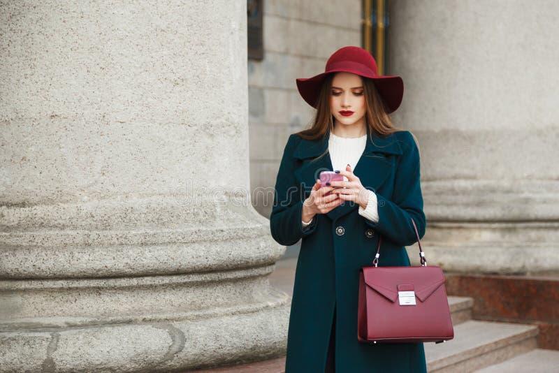 La señora bastante joven de la moda lleva el sombrero y la capa en smartphone clásico del uso del estilo imágenes de archivo libres de regalías