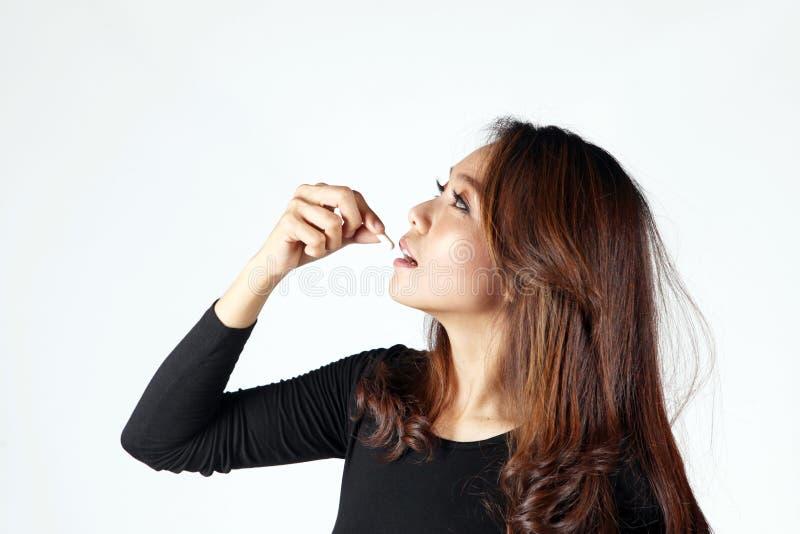 La señora come la píldora para el miedo en la vitamina de la obesidad o de la belleza imagen de archivo libre de regalías