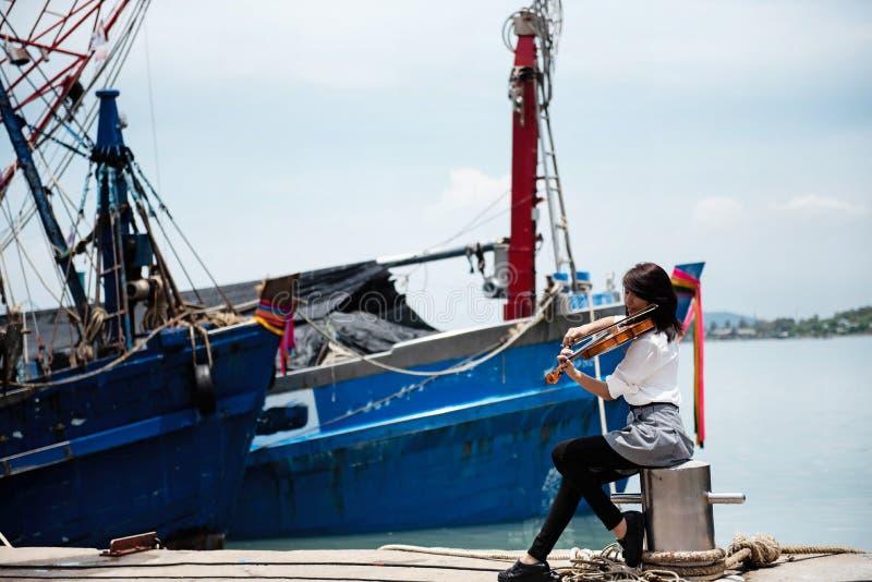 La señora con la camisa blanca está tocando el violín en el habour, cerca del barco de pesca, foto de archivo