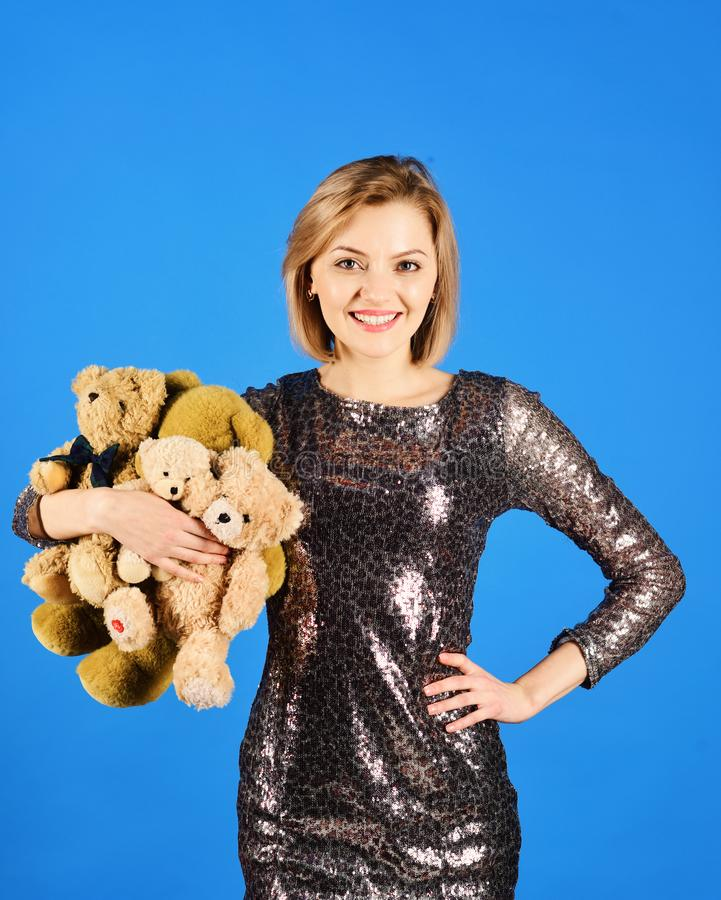 La señora con el pelo rubio abraza osos lindos del juguete foto de archivo
