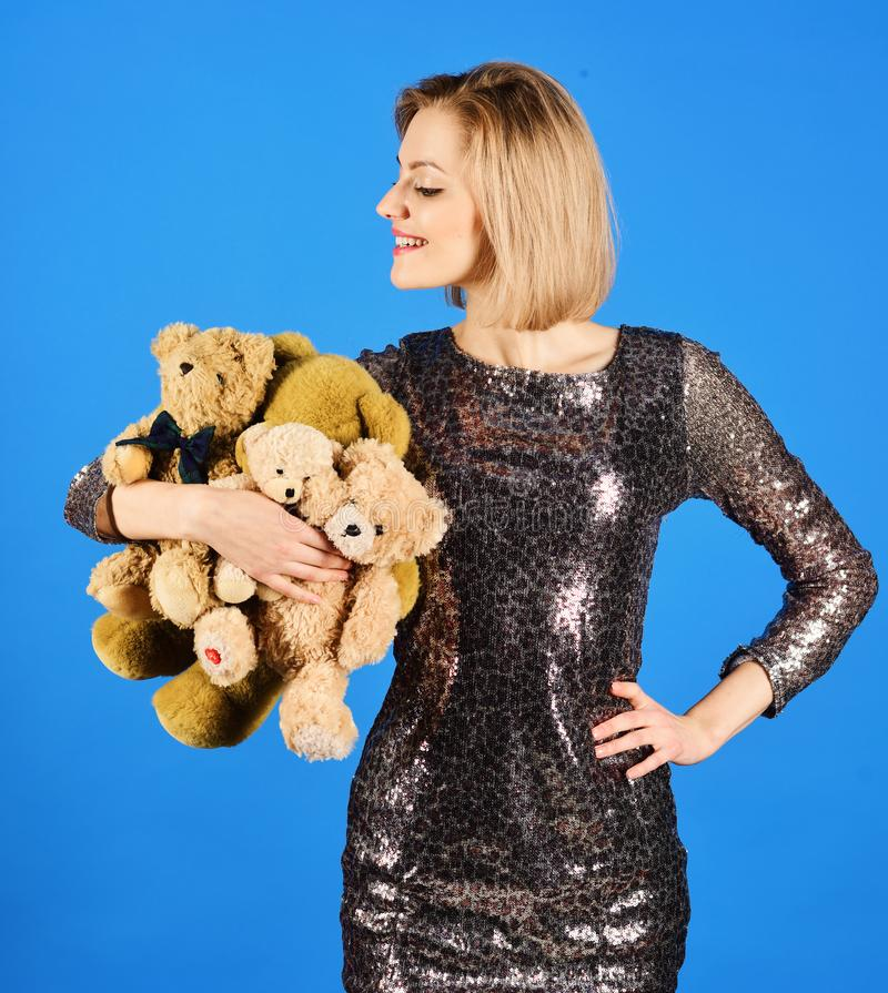 La señora con el pelo rubio abraza osos lindos del juguete fotografía de archivo