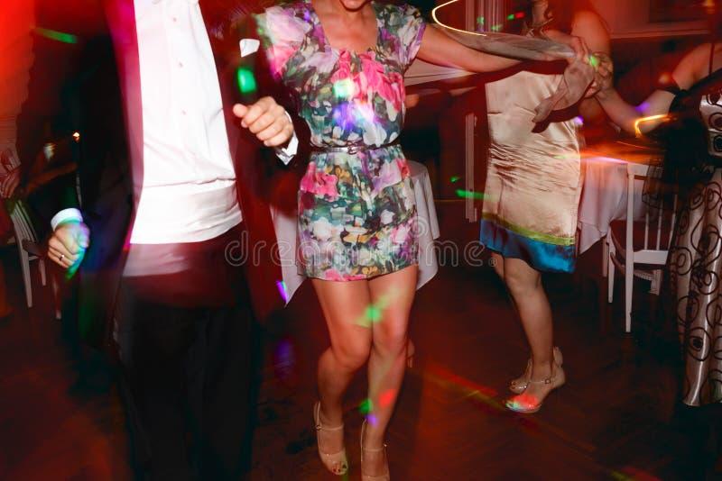 La señora con las piernas bronceadas largas baila en un pasillo del restaurante imagenes de archivo