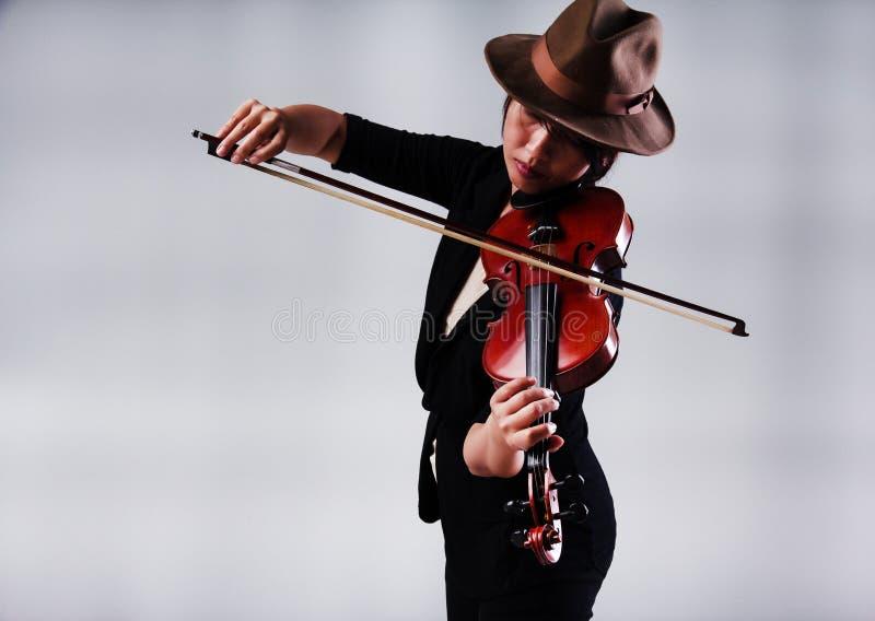 La señora con la mano marrón y el traje negro, tocando el violín, el violinista fotografía de archivo