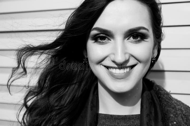 La señora con sonrisa encantadora está presentando en fondo de la pared Retrato urbano blanco y negro de la mujer joven con el pr fotos de archivo