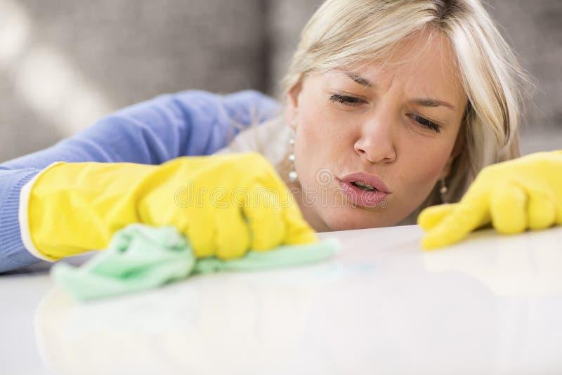 La señora de la limpieza quita manchas de la tabla foto de archivo