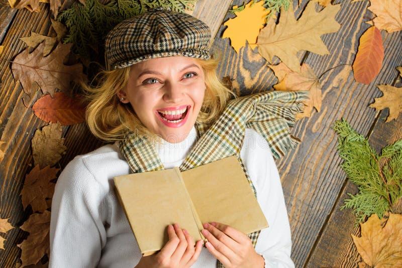 La señora de la mujer en sombrero a cuadros y bufanda leyó el libro La muchacha en equipo del vintage disfruta de la literatura E imagen de archivo libre de regalías