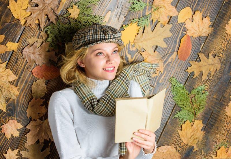 La señora de la mujer en sombrero a cuadros y bufanda leyó el libro La muchacha en equipo del vintage disfruta de la literatura Q imagenes de archivo