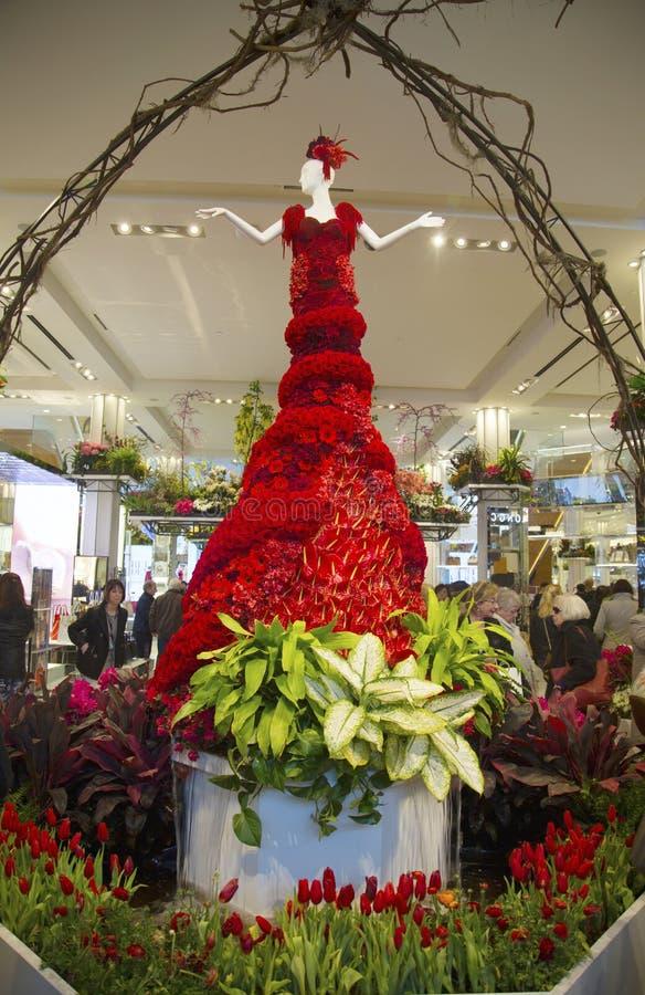 La señora de 14 pies de alto que sorprende en rojo es un pedazo de centro de la exhibición floral famosa de Macy foto de archivo