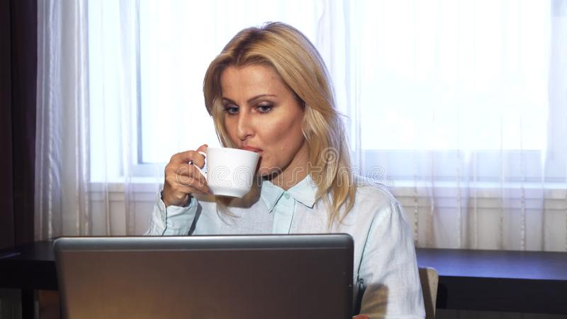 La señora del negocio bebe el café mientras que se sienta en su ordenador portátil imagenes de archivo