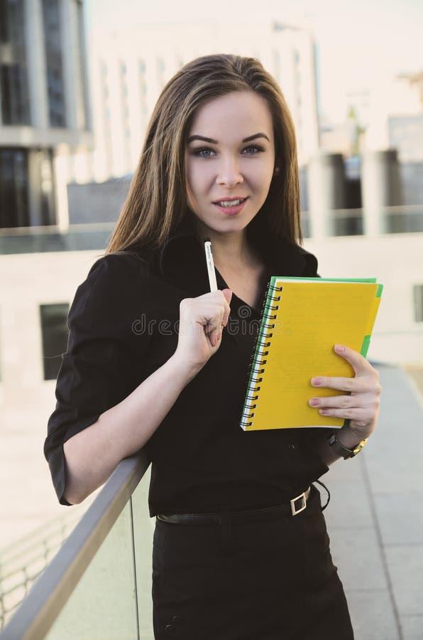 La señora del negocio sostiene un cuaderno, sonrisas, miradas en la cámara fotografía de archivo libre de regalías