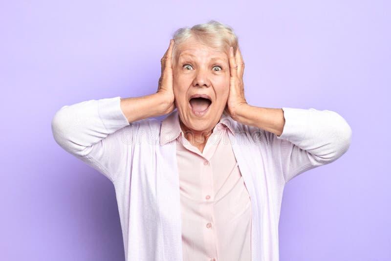 La señora emocional en blusa y camisa guarda las manos en cara que grita fotografía de archivo libre de regalías