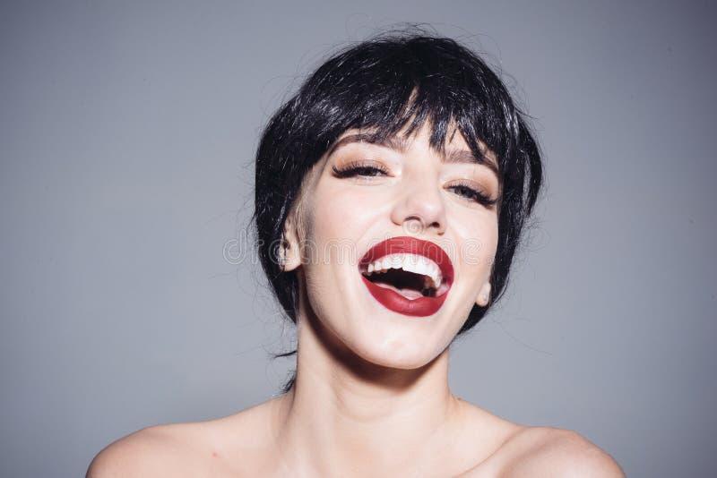 La señora en peluca negra con compone en fondo gris Muchacha en la cara sonriente feliz que presenta con los hombros desnudos Her foto de archivo