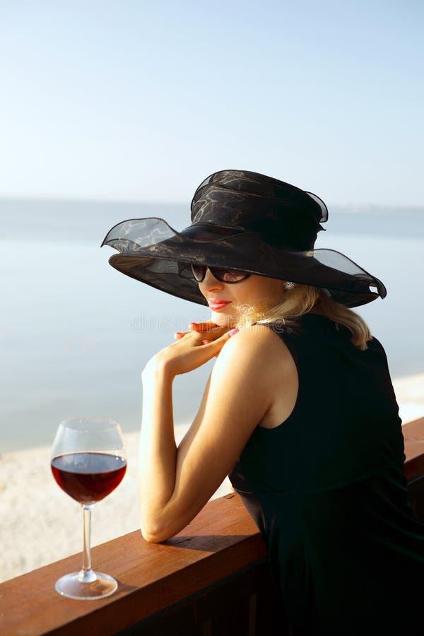 La señora en un sombrero con un vidrio de vino imagen de archivo libre de regalías