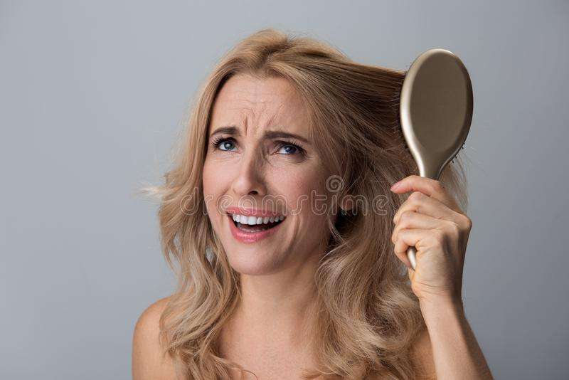 La señora enfadada está sosteniendo el cepillo para el pelo imagen de archivo
