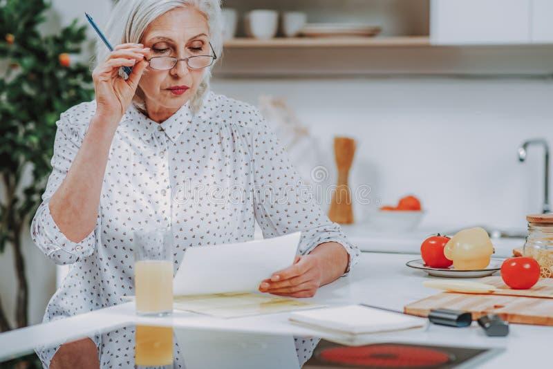 La señora envejecida está leyendo notas sobre la fabricación del plato en casa imagenes de archivo