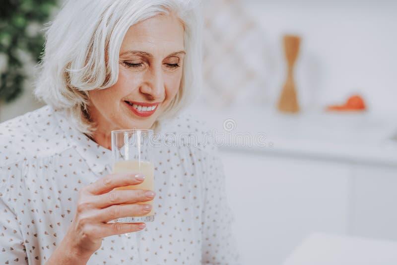 La señora envejecida Relaxed está bebiendo el jugo en casa fotos de archivo