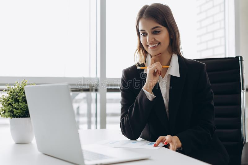 La señora hermosa del negocio está mirando el ordenador portátil y está sonriendo mientras que trabaja en oficina Concentrado en  imagen de archivo libre de regalías