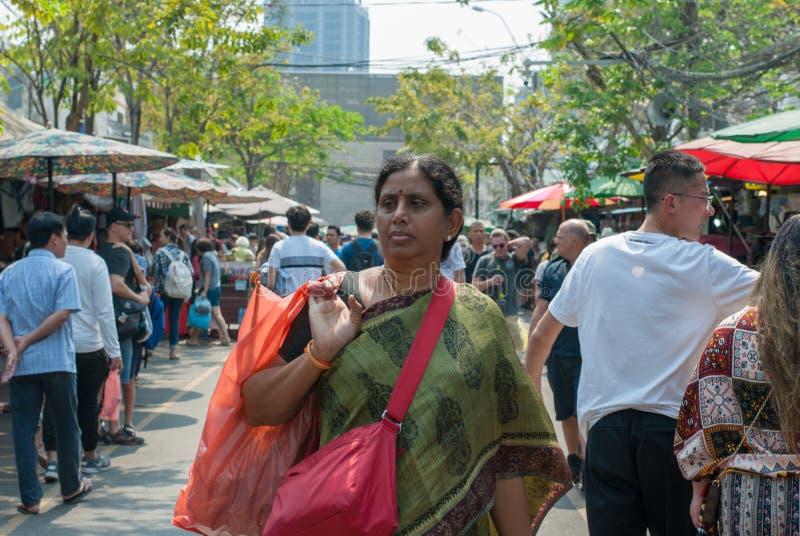 La señora india está llevando la bolsa de plástico que busca cosas para comprar imagenes de archivo