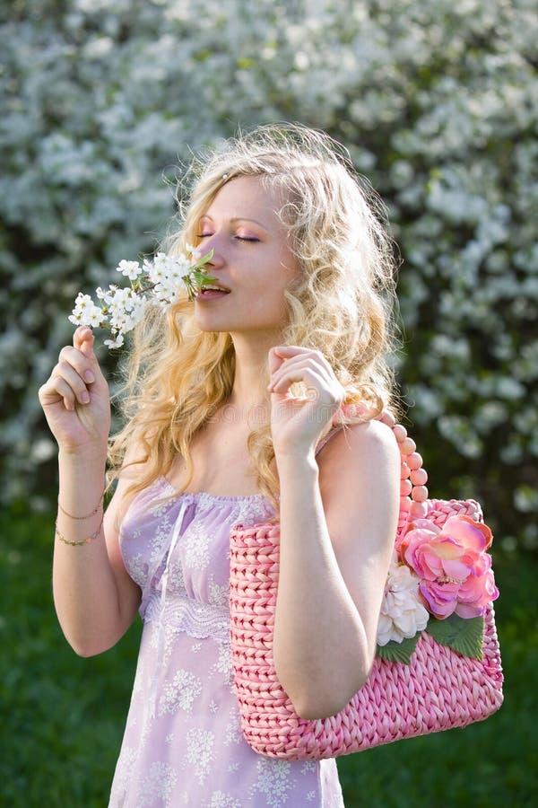 La señora joven con la cereza que huele del bolso rosado florece fotos de archivo libres de regalías