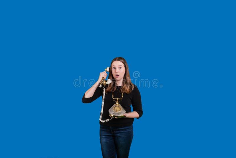 La señora joven en un teléfono atado del vintage sorprendió mirada en su cara foto de archivo