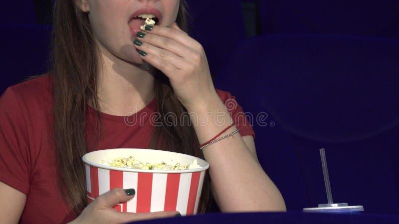 La señora joven está comiendo las palomitas durante la investigación foto de archivo libre de regalías