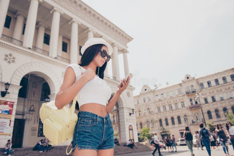 La señora joven está hojeando en su PDA mientras que en paseo afuera en imágenes de archivo libres de regalías