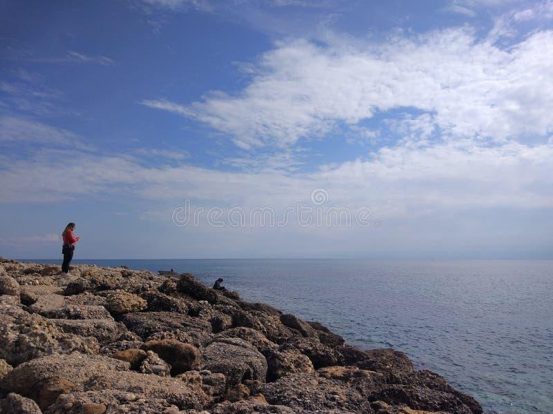 La señora joven está mirando el mar imagen de archivo