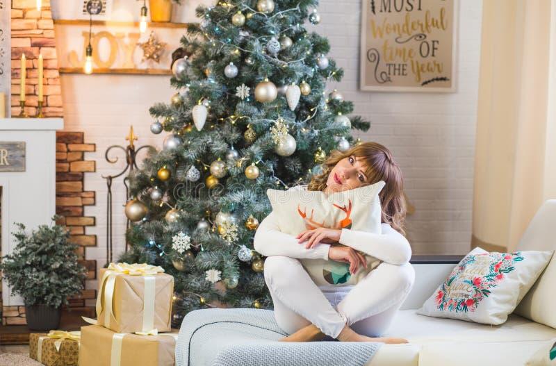 La señora joven feliz con el pelo rizado se sienta cerca del árbol de navidad imagen de archivo