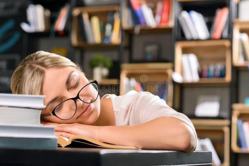 La señora joven se cae dormido mientras que estudia imagen de archivo